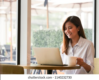 Close up asain woman hands with creadit card and laptop in coffee shop.