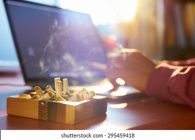 Close up of ashtray full of cigarette, with man in background working on laptop computer and smoking indoors on early morning. Concept of addiction and abuse of nicotine.