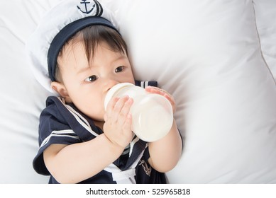 Close up of Asian baby infant drinking mother breast feeding from bottle