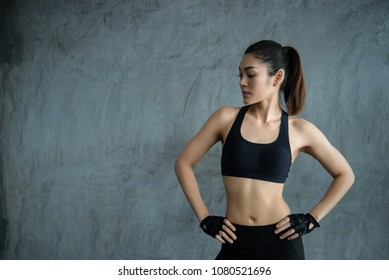 Close up asian beautiful sportswoman wear sport bra on wall of gym,Thailand love health,Slim woman workout concept
