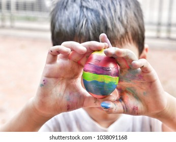 Close up of  asian boy with colorful stained hands holding rainbow ester egg to obscure his face. Happy ester holiday.