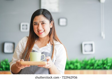 close up asian business owner woman holding cup of coffee on wood tray for serving to customer in her shop, drink and beverage concept.