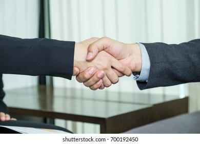Close up asian business people handshake deal with agreement at office