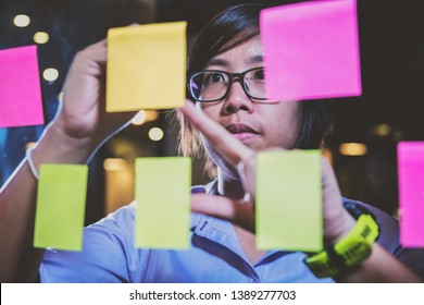 close up asian businesswoman writing a plan on sticky notes