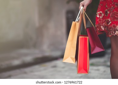 Close Up Asian Chinese Woman in Cheongsam Traditional Red Dress Holding Shopping Bag in Chinese New Year Festival