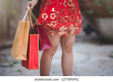 Close Up Asian Chinese Woman in Cheongsam Traditional Red Dress Holding Shopping Bag in Chinese Lunar New Year Festival