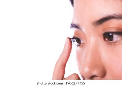 close up of Asian female eye touching eyelashes. isolated on white background with copy space.