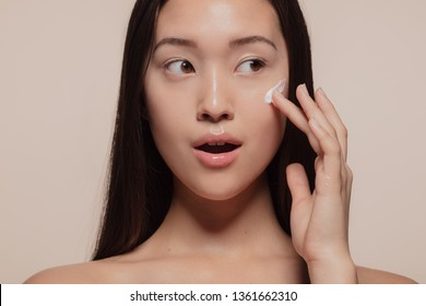 Close up of a asian female model applying moisturizer to her face and looking away. Woman applying moisturizer cream on her pretty face against beige background.