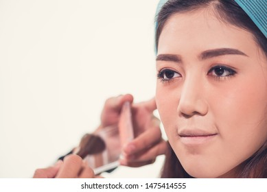 Close up of Asian female model face with  putting makeup  by makeup artist