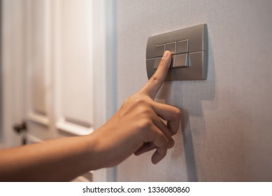 Close up of Asian female right hand is turning on or off on grey light switch over textile texture wall in Luxury house. Copy space.