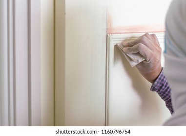 Close up asian female worker in casual using sand paper rubbing door for painting work in house improvement project