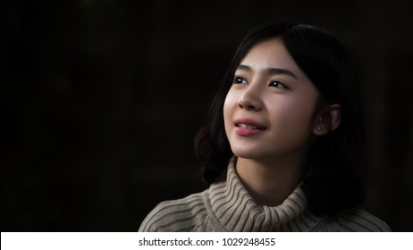 Close up of Asian girl looking up In the dark background