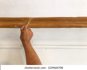 Close up asian hand using brush to dap lacquer for touch up on teak wooden border, diy house improvement