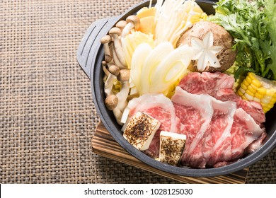Close up of Asian hot pot with a lot of vegetables and beef, on a brown mat.