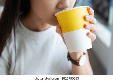 Close up of the Asian lady holding the hot drink paper cup with one hand and sipping the hot beverage - Shutterstock ID 1823950883