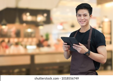 close up asian man barista holding tablet for checking order from customer on blurred coffee cafe shop background , SME business concept