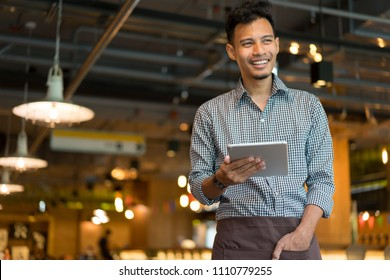 close up asian man barista holding tablet and looking forward at inside restaurant cafe shop background , SME business concept