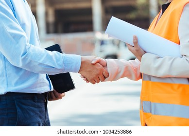 Close up Asian man civil engineer holding laptop and Asian woman architect holding drawing blueprint shaking hands at construction site.