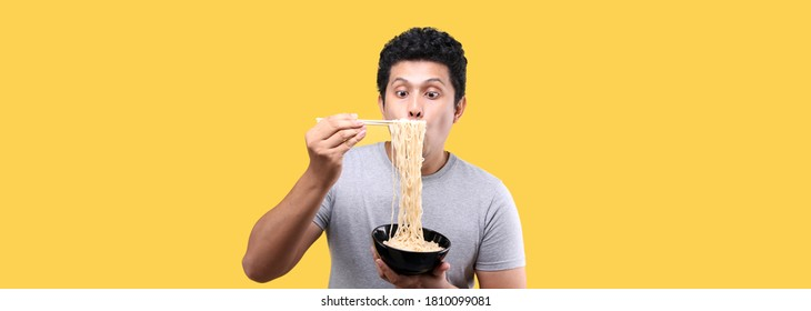 Close up Asian man eating yummy hot and spicy instant noodle using chopsticks and bowl isolated on yellow background in studio With copy space.