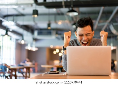 close up asian man exited and happy when watching digital TV on internet at library room in weekend , lifestyle concept