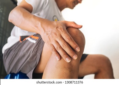 Close up of an asian man holding his knee in pain