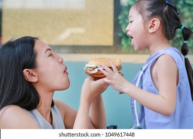 Close up Asian mother with child girl eating a hamburger together.