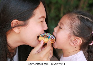 Close up Asian mother and her daughter eating rainbow donut together.