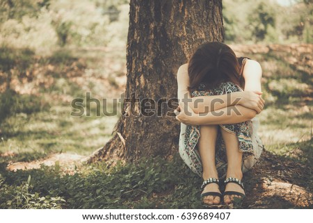 Close up asian sad woman sit under the tree vintage style,heartbreak girl concept
