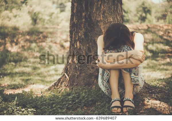 Close up asian sad woman sit under the tree vintage style,heartbreak girl concept