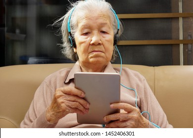 Close up Asian senior or elderly old lady woman enjoy listening to music (using or playing) from tablet. Healthcare, medical and technology concept.