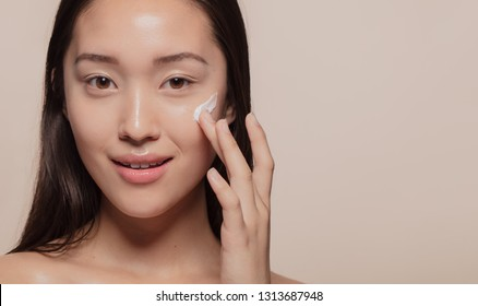 Close up of a asian woman applying moisturizer to her pretty face. Female model putting cream on her glowing face skin.