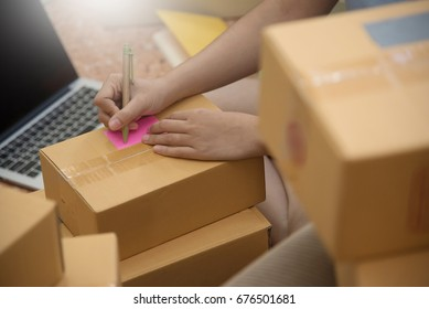 Close up Asian woman checking supplies and writing on cardboard box with laptop in her small warehouse. Own business