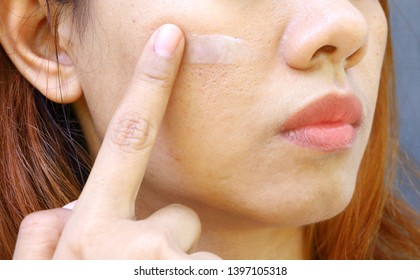 Close up Asian woman face have problem on skin, oily, large and wide pore. The woman use finger to scrape the white cream on her cheek for facial care.