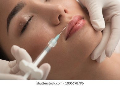 Close up of asian woman face receiving rejuvenation treatment. Doctor hand in glove lifting collagen in lip area
