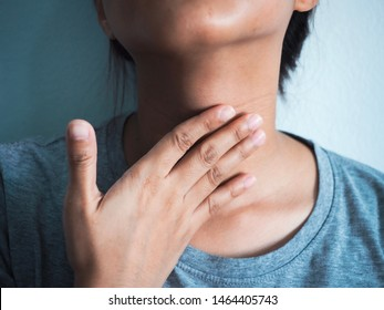 Close up Asian woman hand caught on the neck With a sore throat on a gray background With the concept of health care and medical