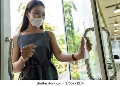 close up of asian woman hand with tissue paper to push restaurant door open reduce hand touching on public place to reduce chance to infection by coronavirus covid-19. New normal lifestyle concept