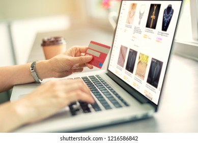 Close up of asian woman hands holding credit card and using laptop computer at coffee shop to perform shopping online by inputting card information for payment method. Ecommerce business concept.