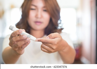 Close up of asian woman hands using lancet on finger to check blood sugar level by glucose meter, Health care medical and check up, diabetes, glycemia, and people concept