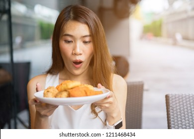 close up asian woman holding dish of fried chicken with happy surprise  face at restaurant for brunch meal , healthy life concept