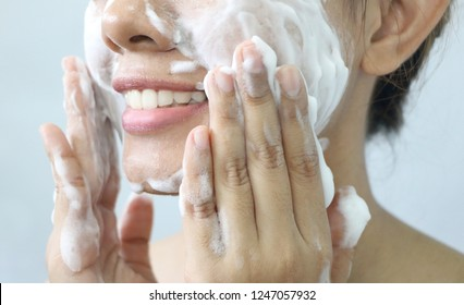 Close up Asian woman smile and washing face by make bubble facial foam and cleansing her face skin