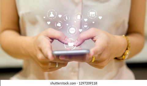 close up asian woman using smartphone for choosing item in marketplace on store website with virtual interface of shopping online (b2b) technology concept