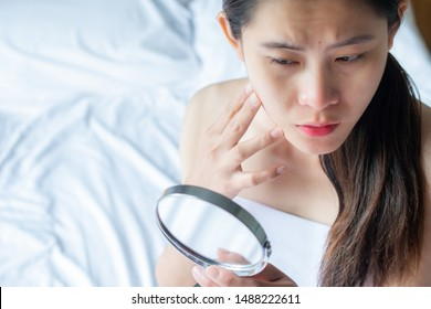 Close up of Asian woman worry about her face when she saw the problem of acne and scar by the mini mirror. Conceptual shot of Acne & Problem Skin on female face.