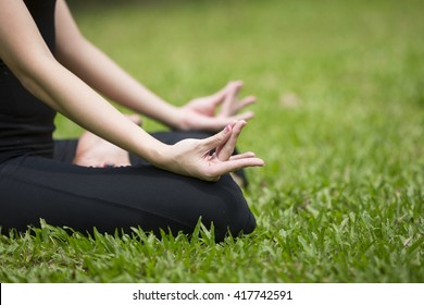 Close up of an Asian woman's hands practicing yoga in a garden. Healthy lifestyle and relaxation concept.
