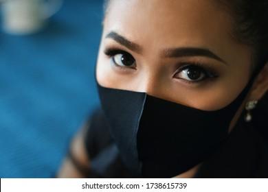 close up asian women wearing black protection face mask. bold eyes make up. blue background