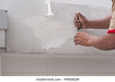 Close up asian worker hand scrape old paint from cement wall by putty trowel