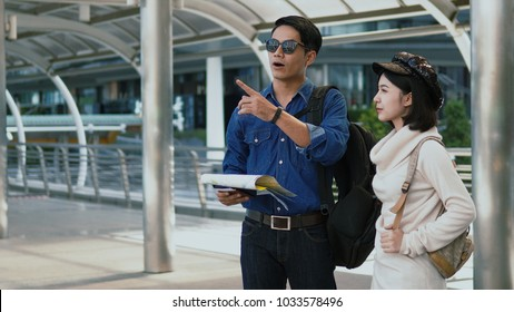 Close up Asian young man hold a paper map in hand and point forward a destination to go with pretty woman looking over there, copy space