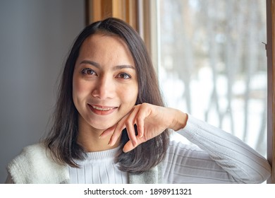 close Up Asian Young Woman smiling and looking at camera on Blurred Background.
