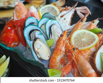 Close up assorted fresh cooked cold seafood as shrimps, prawns, New Zealand mussels, mussels, oyster, rock lobster, lobster claw with yello leomon in oval shaped dish or plate on ice on wooden table