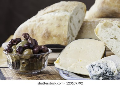 Close up of assorted olives with rustic breads and cheese