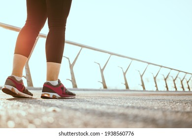 Close up of athlete woman legs walking on bridge in the morning, wearing grey and pink sneakers and black sports leggings. Weight loss cardio goal achievement challenge. Sport and healthy lifestyle.
